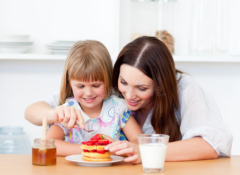 Merry little girl and her mother having breakfast stock photos