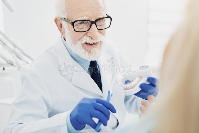 Merry male dentist demonstrating teeth cleaning royalty free stock photo