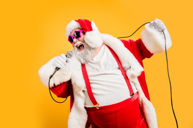 Merry x-mas carols from crazy overweight white hair christmas grandfather hold microphone sing song on noel time stock images