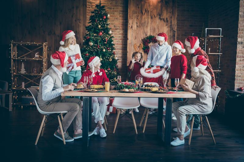 Merry x-mas family meeting on christmas eve joyful man in santa claus hat cap hold sack bag give giftboxes wish follow royalty free stock images