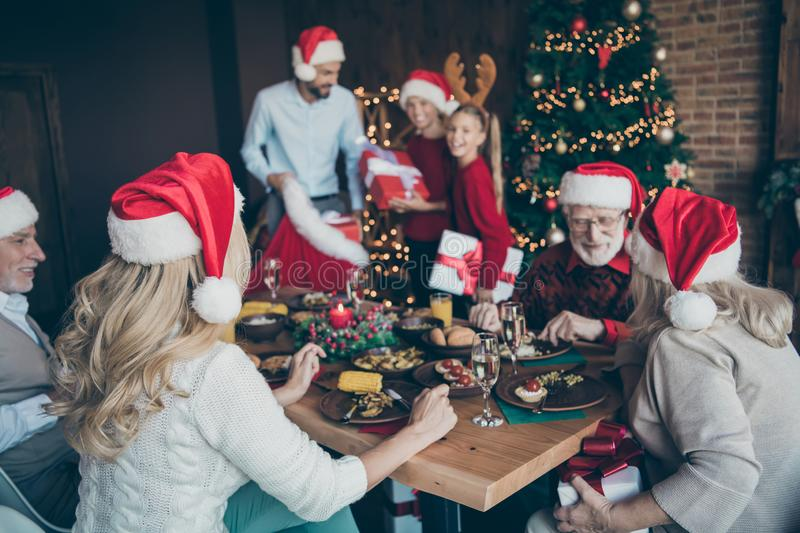 Merry x-mas noel meeting of large family back side photo old people sit table speak talk eat feast wear red santa claus. Cap hat father, have fun with small stock photography