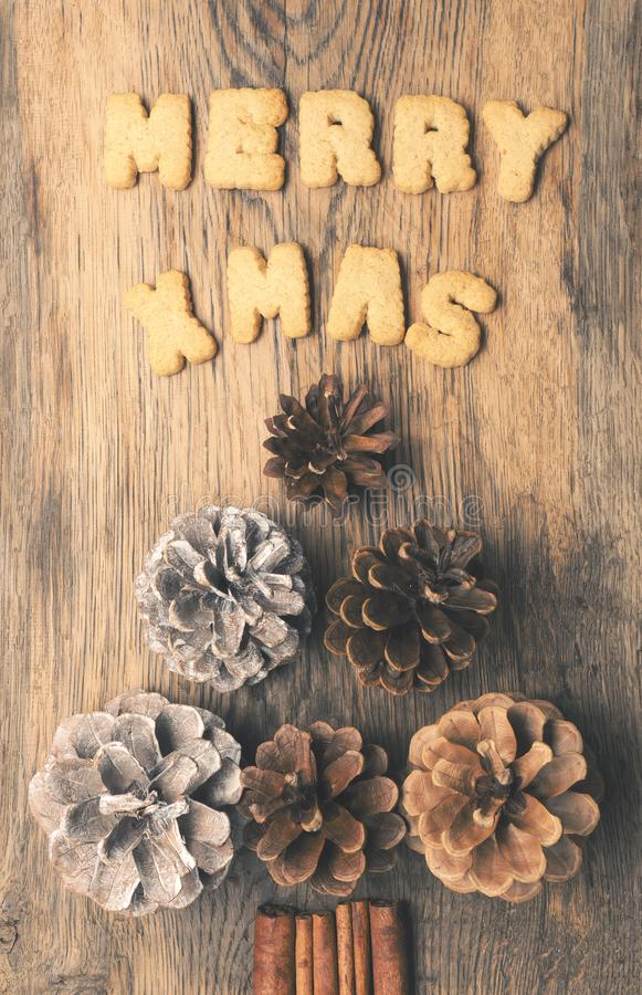 Merry X-Mas with pine cones. Christmas tree shape of pine cones with the words Merry XMas on a rustic wooden plank stock images