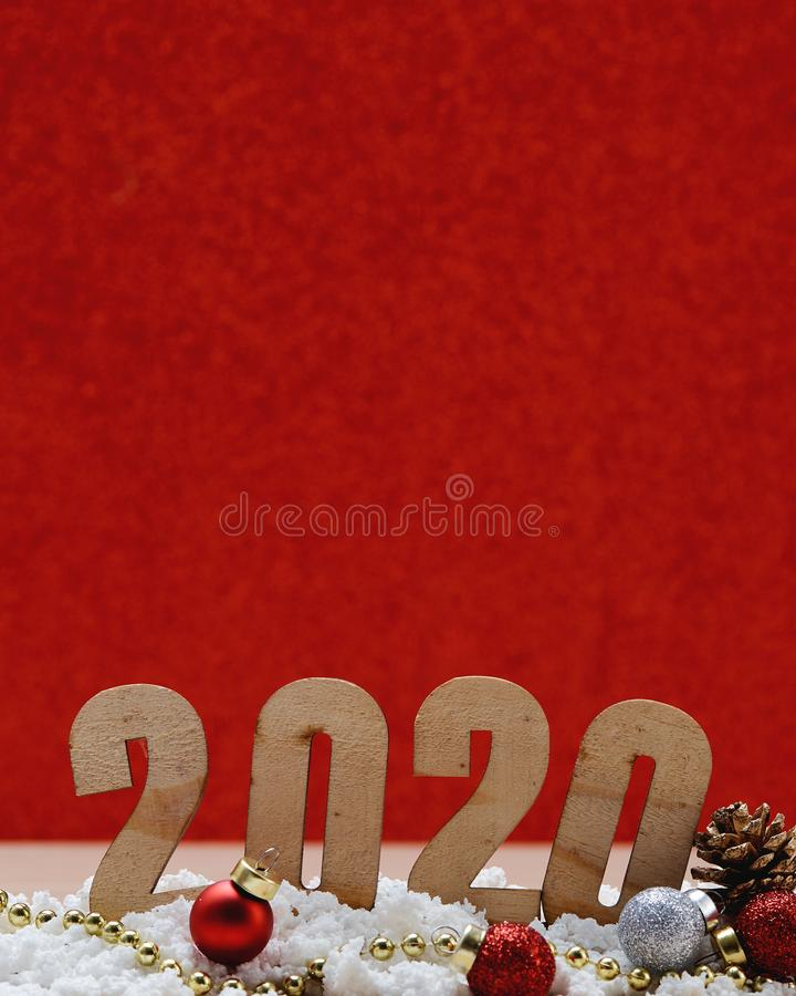 Merry New Year 2020 Christmas with celebration decorations. Snow pile on wooden table with a glittery red background, minimal copy space for text royalty free stock photo
