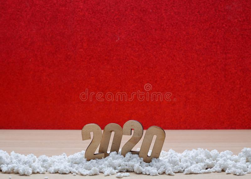 Merry New Year 2020 Christmas with celebration decorations. Snow pile on wooden table with a glittery red background, minimal copy space for text royalty free stock photos