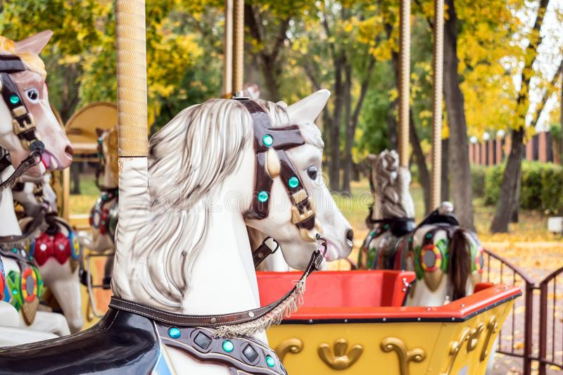 A merry-round-go Carousel Horse close up in Autumn park. Old woo. Den Retro carousel white horse. carnival cheerful walk. CloseUp of colorful carousel ( stock photo