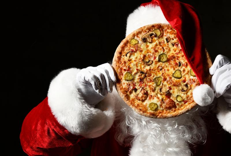 Merry Santa Claus is holding big tasty pizza in front of his face, hiding behind it. New year and Merry Christmas. Merry Santa Claus is holding big tasty pizza royalty free stock image