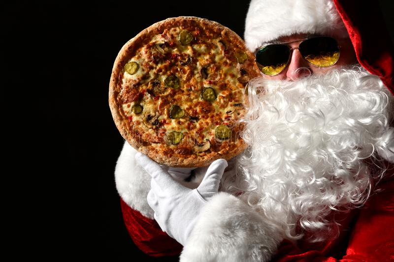 Merry Santa Claus is holding big tasty pizza in at his face, comparing. New year and Merry Christmas. Fast food concept royalty free stock photo
