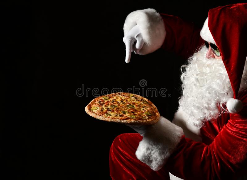 Merry Santa Claus is pointing down at big tasty pizza he is holding on his open palm. New year and Merry Christmas. Merry Santa Claus is pointing down at big royalty free stock images