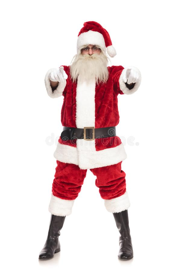 Merry santa claus pointing fingers while standing with parted fe. Et on white background stock photos