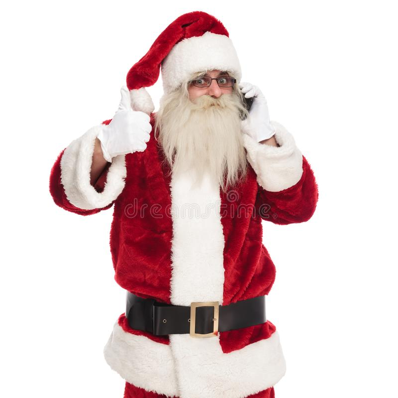 Merry santa claus speaks on phone and makes ok sign royalty free stock photos