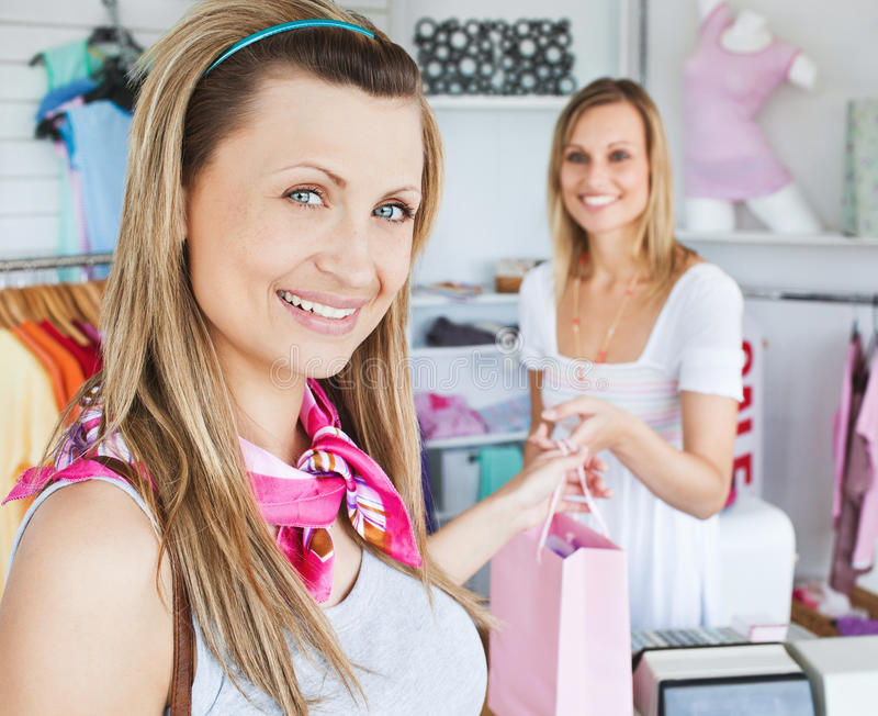 Merry woman getting shopping bags from saleswoman. Merry young woman getting shopping bags from the saleswoman in a clothes store stock image