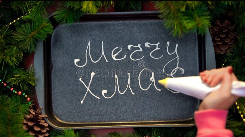 Merry Xmas, female hand writing phrase with cream on baking tray, preparations stock photo