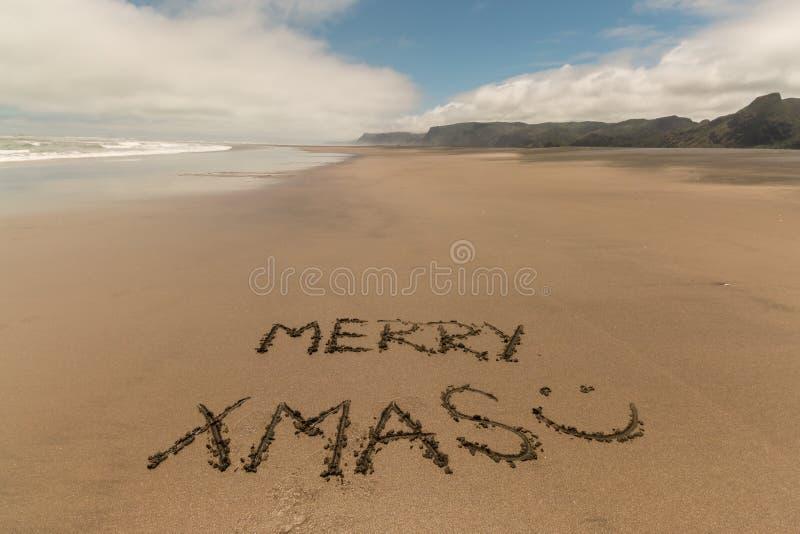 Merry xmas handwritten in sand. On Karekare beach, New Zealand stock image