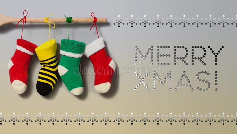 Merry Xmas text invitation card. Hanging Christmas socks on gradient gray beige background. Colorful stocking decoration royalty free stock images