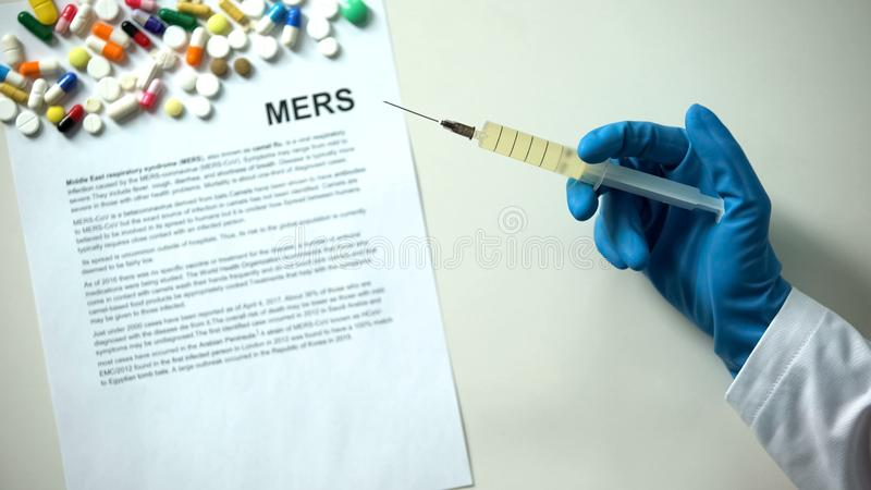 MERS diagnosis written on paper hand holding medication in syringe treatment. Stock photo stock photography