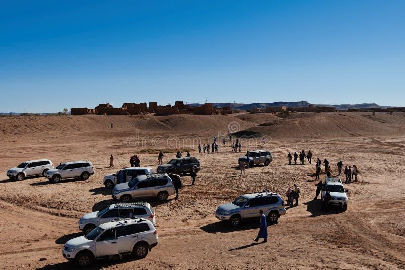 Merzouga,摩洛哥- 2018年12月05日:游人牧群在沙漠中间的有一小镇的在背景中 免版税库存照片
