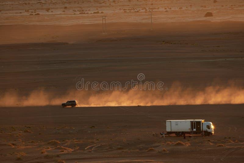 Merzouga,摩洛哥- 2018年12月04日:载重汽车autocaravana,y coche levantando polvo Al atardecer en el desierto 免版税库存照片