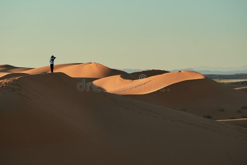 Merzouga, Marocco - 5 dicembre 2018: una persona in mezzo al deserto, sopra una duna immagini stock libere da diritti