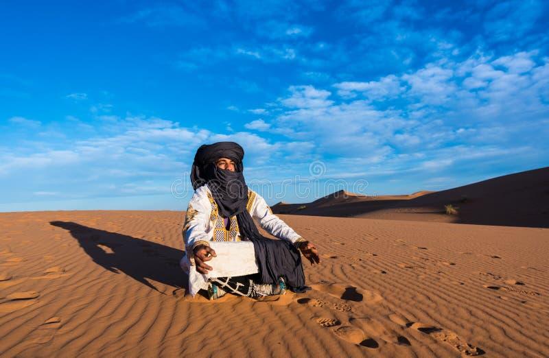 Merzouga Marocko - Oktober 16, 2018: Tuaregman som mediterar i dyerna för ergChebbi sand i Sahara Desert arkivbilder