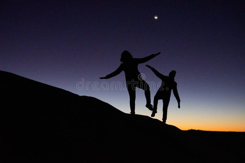 Merzouga, Marokko - December 04, 2018: backlight twee mensen die een duin met een zonsopgang beklimmen stock foto's