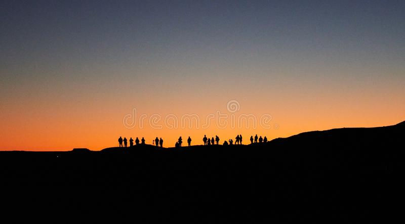 Merzouga Maroko, Grudzień, - 04, 2018: backlight mnóstwo ludzi czeka wschód słońca fotografia stock