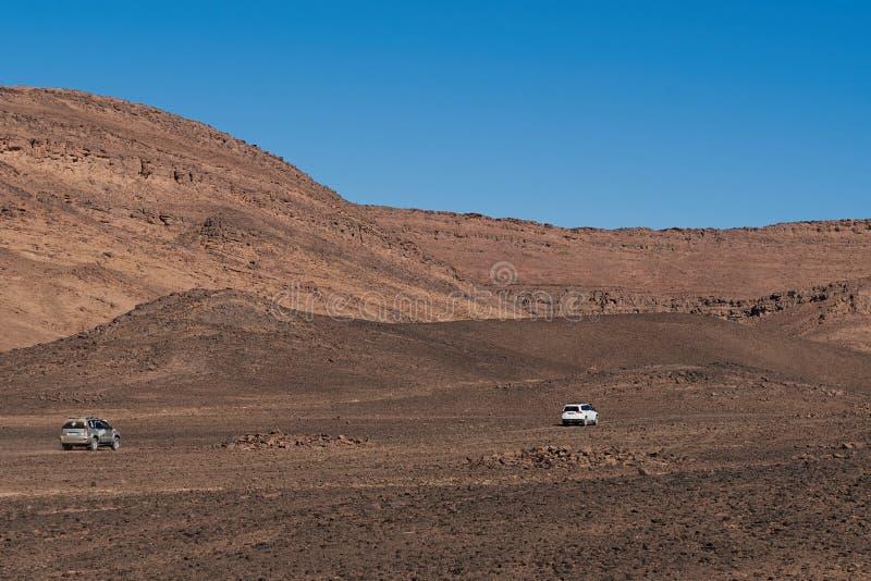 Merzouga, Marruecos - 5 de diciembre de 2018: dos coches 4x4 en el medio del desierto árido imagen de archivo