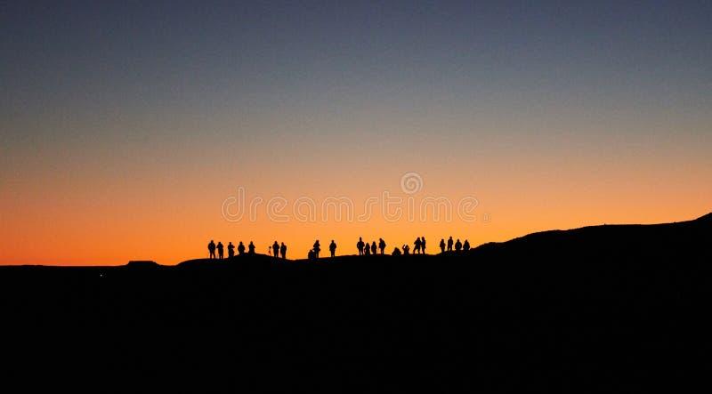 Merzouga, Marruecos - 4 de diciembre de 2018: haga excursionismo a mucha gente que espera la salida del sol fotografía de archivo