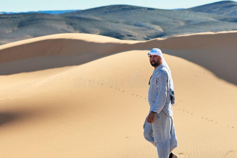 Merzouga, Marruecos - 5 de diciembre de 2018: joven el mirando del desierto del EL del por del caminando del berebere un ¡Mara de imagen de archivo libre de regalías