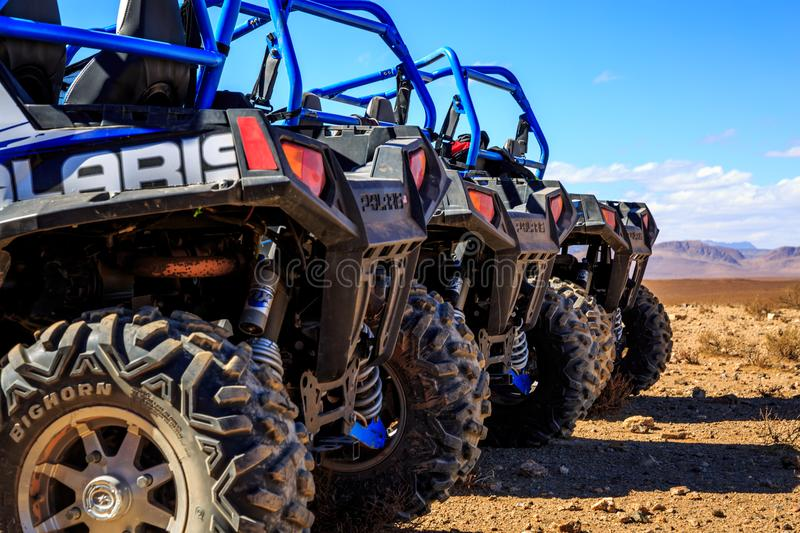 Merzouga, Morocco - Feb 21, 2016: Close-up of wheel of Blue Polaris RZR 800. Aligned and stationed with no pilot in Morocco desert near Merzouga. Merzouga is stock photos