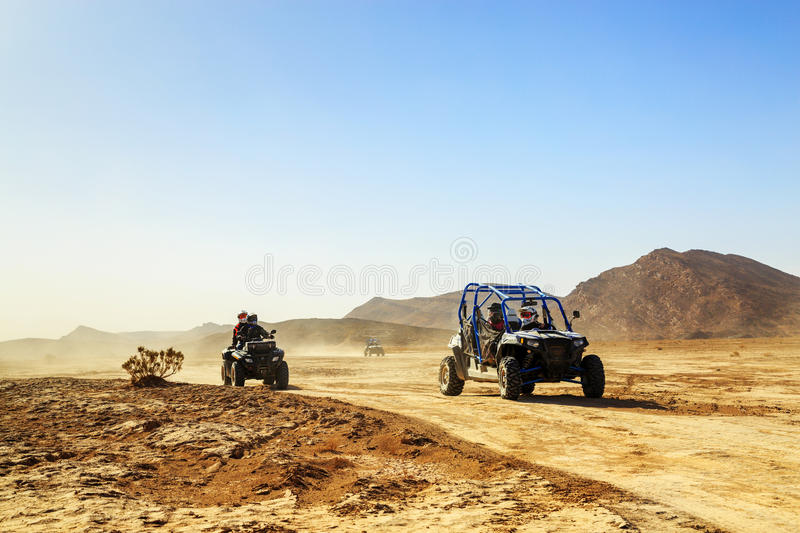 Merzouga, Morocco - Feb 24, 2016: convoy of off-road vehicles (RZR, Quad and motorbikes) in Morocco desert near royalty free stock photography