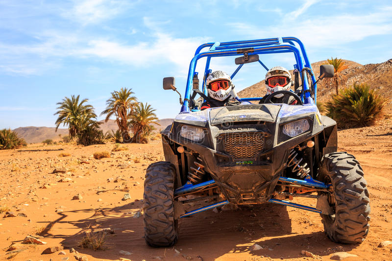 Merzouga, Morocco - Feb 26, 2016: front view on blue Polaris RZR 800 with it's pilots in Morocco desert near Merzouga. Merzouga is. Famous for its dunes, the royalty free stock images