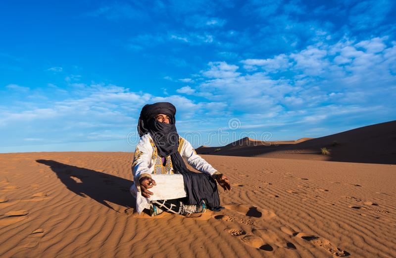 Merzouga, Morocco - October 16, 2018: Tuareg man meditating in the Erg Chebbi sand dunes in the Sahara Desert stock images