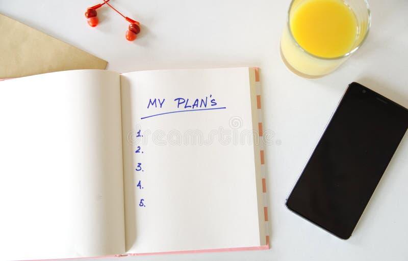 Mes buts ?crits dans un carnet Positionnement de bureau t?l?phone, jus, stylo, t?l?phone et journal intime mes plans, l'espace po images libres de droits