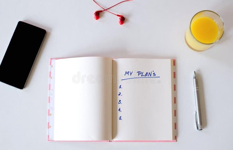 Mes buts ?crits dans un carnet Positionnement de bureau t?l?phone, jus, stylo, t?l?phone et journal intime mes plans, l'espace po photo libre de droits