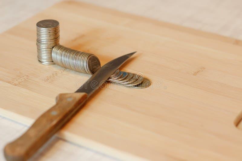 Mes die een stapel van muntstuk snijden Concept besnoeiingen op de begroting, besparingen, r stock foto's