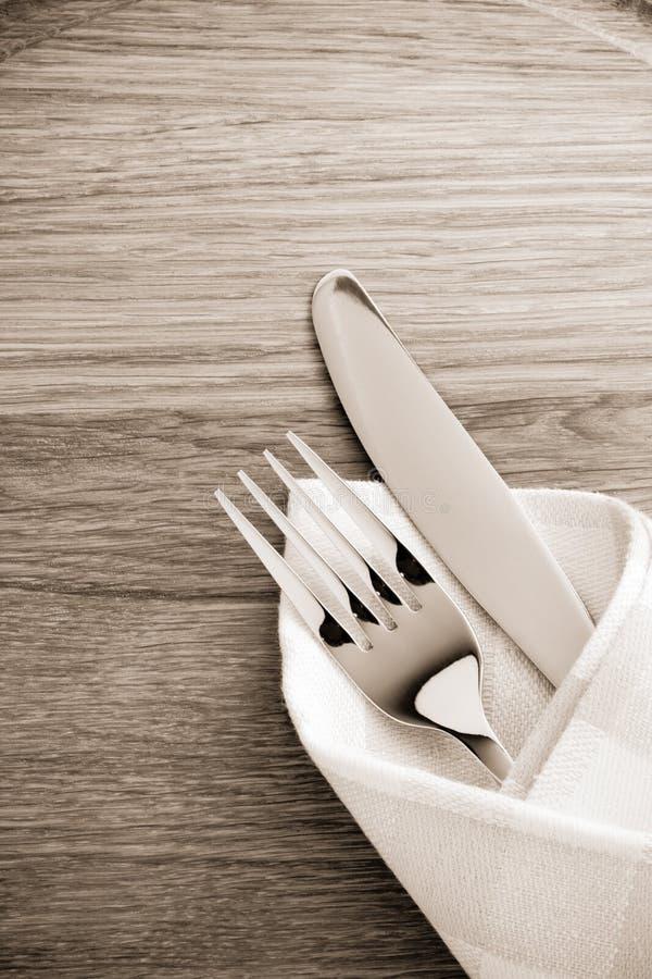 Mes en vork bij servet op hout royalty-vrije stock afbeelding