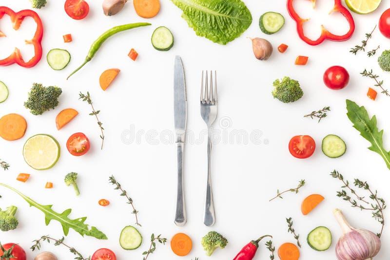 Mes en vork in cirkel van gesneden groenten stock afbeeldingen