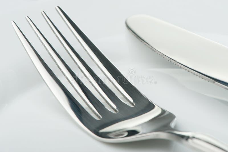 Mes en vork op een plaat stock afbeeldingen