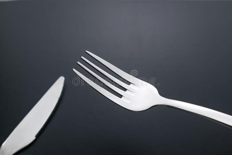 Mes en vork op zwarte achtergrond stock foto's