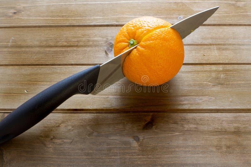 Mes het snijden door een sinaasappel van de keukenlijst vóór ontbijt stock foto