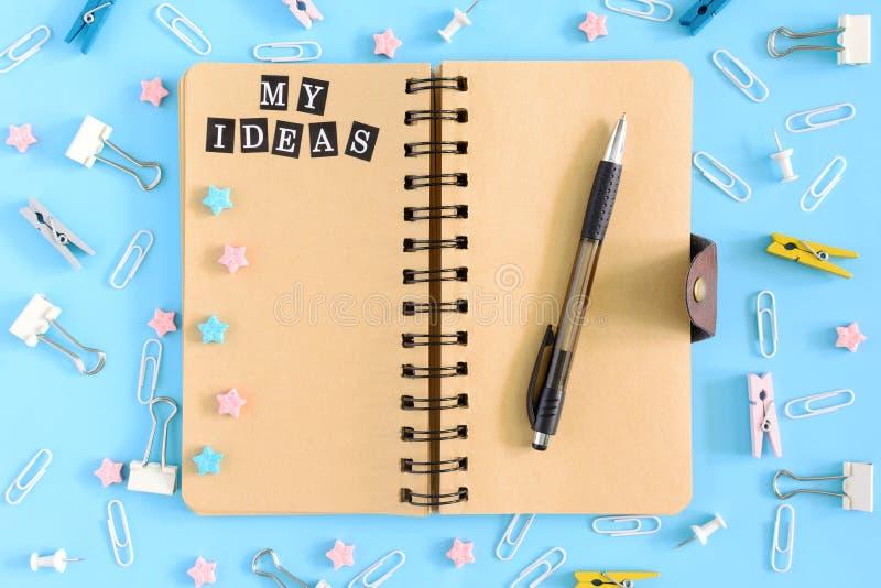Mes idées Bloc-notes des ressorts avec les pages brunes sur un fond bleu Des fournitures de bureau sont dispersées chaotiquement  image stock