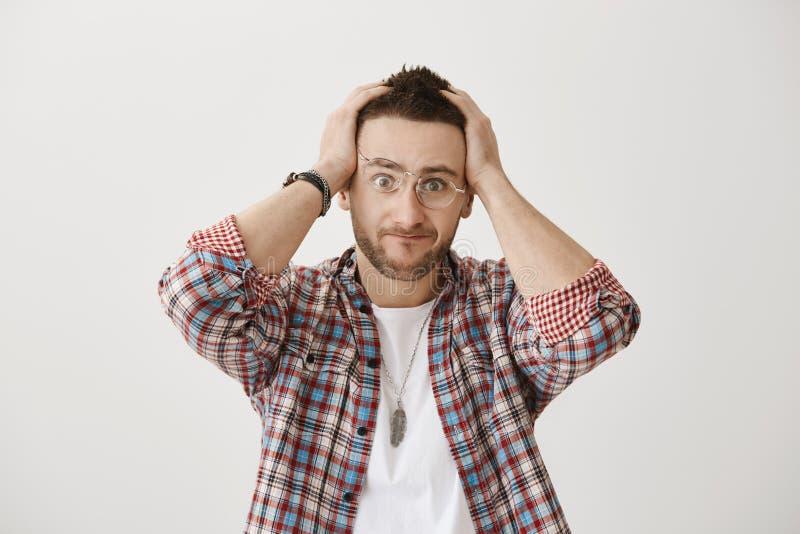 Mes maux de cerveau de votre cri perçant Tir de studio de mâle caucasien attirant tracassé et contrarié avec la barbe, portant photographie stock