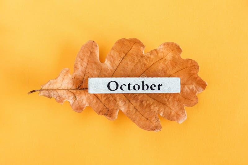 Mes natural Octubre en la hoja de roble de otoño sobre fondo amarillo. Vista superior Espacio para copiar Diseño plano Estilo mà foto de archivo libre de regalías