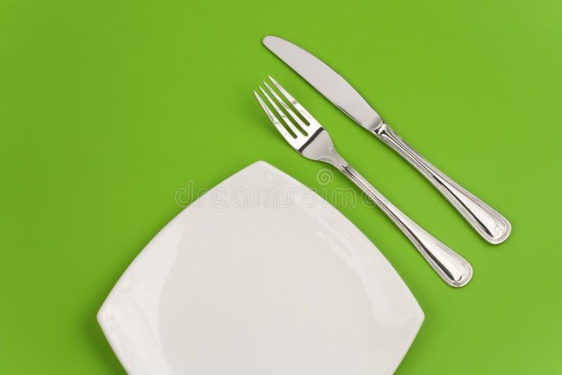 Mes, vierkante witte plaat en vork op groen royalty-vrije stock foto's