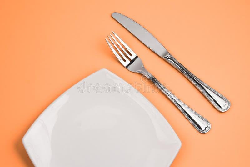 Mes, vierkante witte plaat en vork op roze royalty-vrije stock afbeeldingen