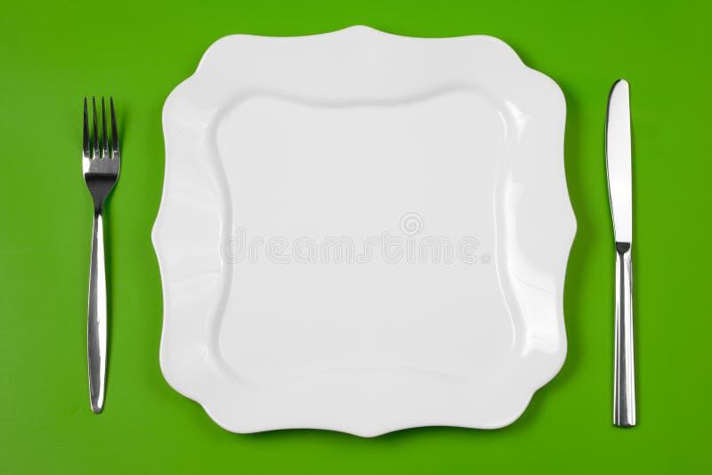 Mes, voorgestelde witte plaat en vork op groen stock foto