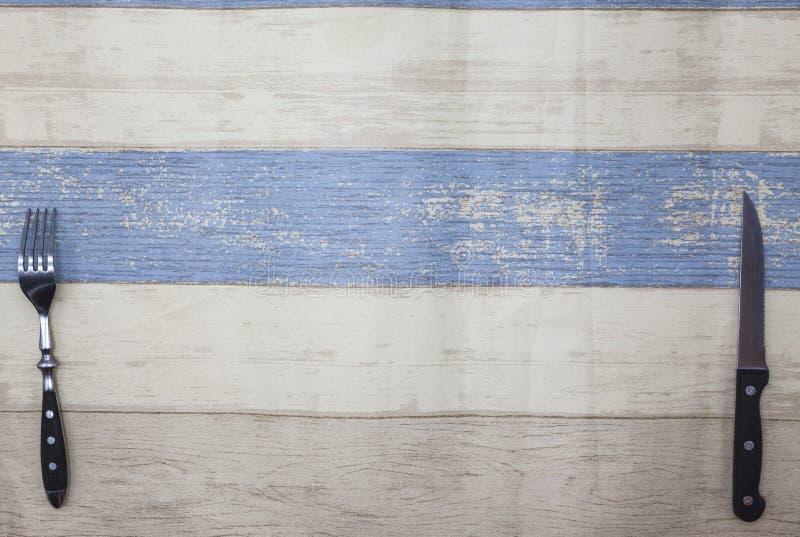 Mes, vork die op een lichte houten achtergrond van de lijst liggen De stijl houten lijst van de Provence, achtergrond voor menu,  royalty-vrije stock afbeeldingen