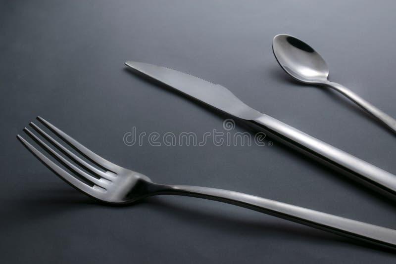 Mes, vork en theelepeltje op zwarte achtergrond stock foto's