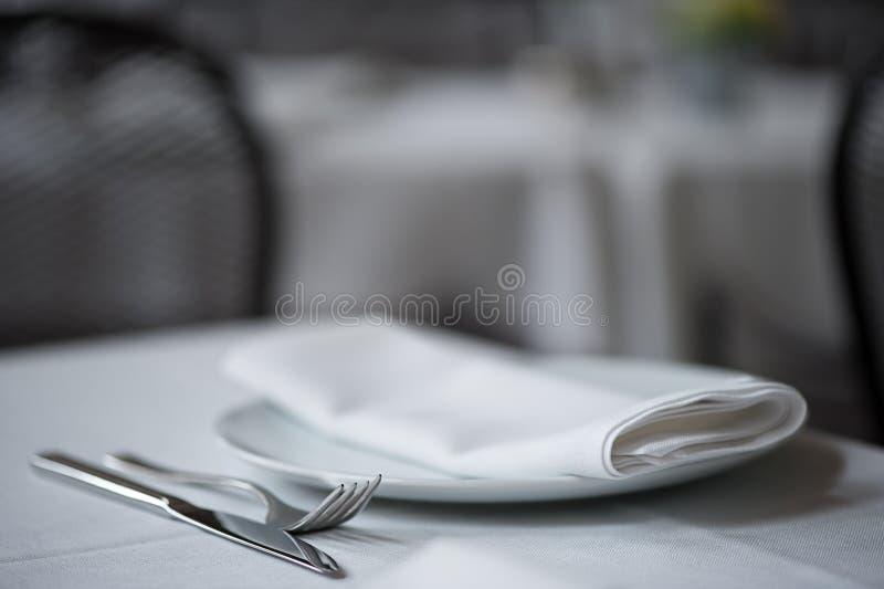 Mes, vork, plaat en gevouwen servet op witte lijstdoek stock fotografie