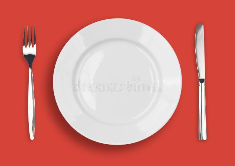 Mes, witte plaat en vork op rood stock afbeelding
